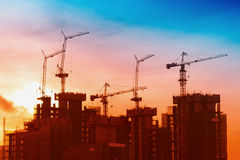 Industrial landscape with silhouettes of cranes on the sunrise b Stock Photography