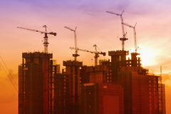 Industrial landscape with silhouettes of cranes Stock Photos