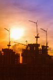 Industrial landscape with silhouettes of cranes Royalty Free Stock Photo