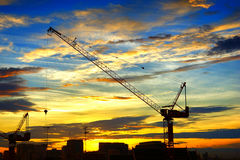 Industrial landscape with silhouettes of cranes on Royalty Free Stock Photo