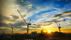 Industrial landscape with silhouettes of cranes on Royalty Free Stock Photography