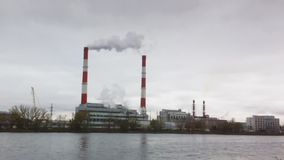 Industrial landscape - thermal power plant over the river, smoke from tube. Wide angle stock video