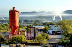 Industrial Landscape. An industrial landscape with a vermilion tower, buildings, and industrial smoke from some distant factory in the industrial district of Royalty Free Stock Photo