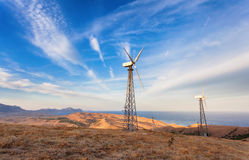 Industrial landscape with wind turbine generating electricity in mountains at sunset Royalty Free Stock Photos
