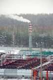 Industrial landscape. Winter industrial landscape oil refinery in the forest Stock Image
