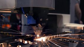 Industrial laser cutter with sparks. The programmed robot head cuts with the aid of a huge sheet of metal temperature. A