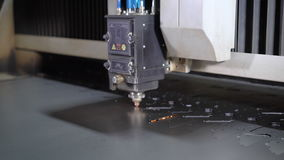 Industrial laser cutter with sparks. The programmed robot head cuts with the aid of a huge sheet of metal temperature stock footage