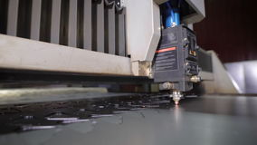 Industrial laser cutter with sparks. The programmed robot head cuts with the aid of a huge sheet of metal temperature stock video footage