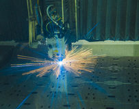 Industrial Laser cutting processing manufacture technology of flat sheet metal steel material with sparks. Laser cut metal splashes Royalty Free Stock Images
