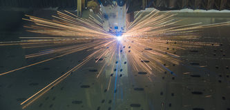 Industrial Laser cutting processing manufacture technology of flat sheet metal steel material with sparks. Laser cut metal splashes Stock Photo