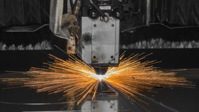 Industrial Laser cutting processing manufacture technology of flat sheet metal steel material with sparks. Laser cut metal splashes Royalty Free Stock Photo