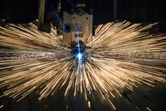 Industrial Laser cutting processing manufacture technology of flat sheet metal steel material with sparks. Laser cut metal splashes Stock Image