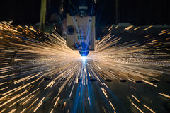 Industrial Laser cutting processing manufacture technology of flat sheet metal steel material with sparks. Laser cut metal splashes Stock Photos