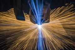 Industrial Laser cutting processing manufacture technology of flat sheet metal steel material with sparks. Laser cut metal splashes Stock Images