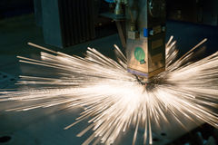 Industrial laser making holes in metal sheet. During production process of manufacturing parts stock image
