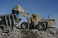 Industrial loader dumping aggregates in crusher Stock Photos