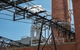 An outside industrial conveyer belt at an old tobacco factory with bright blue sky and a brick smoke tower. An industrial looking complex with a conveyer belt royalty free stock image