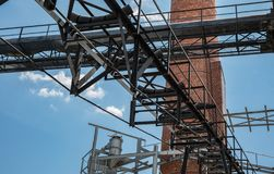 An outside industrial conveyer belt at an old tobacco factory with bright blue sky and a brick smoke tower. An industrial looking complex with a conveyer belt stock photo