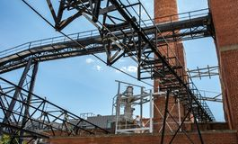 An outside industrial conveyer belt at an old tobacco factory with bright blue sky and a brick smoke tower. stock images