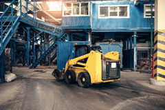 An industrial machine is driving through the plant. Waste processing plant. Recycling and storage of waste for further. Disposal Stock Images