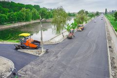 Industrial machine pouring asphalt on city road. Royalty Free Stock Photo