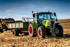 Industrial machinery in agriculture fields - Tractor, Combine and farmers working the fields stock photo