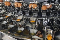 Industrial machinery for broken eggs 2. Industrial facility which automatically break the eggs and separate the whites from the yolks to pasteurization Stock Image