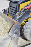 Industrial machinery. At  building site. Detail Backhoe bucket with sand Royalty Free Stock Photo