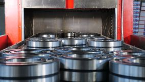 Industrial and machinery concept. A tecnological part of bearing production and assembling. Conveyor in bearing factory. Ready items are being poured with stock video footage