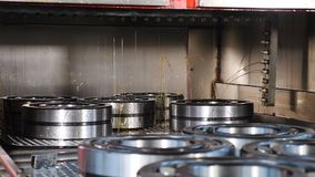 Industrial and machinery concept. A tecnological part of bearing production and assembling. Conveyor in bearing factory. Ready items are being poured with stock footage