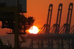Industrial machinery silhouetted against the rising sun. The rising sun has turned the sky orange. The sun is a white flaming ball. Industrial cranes and moving Royalty Free Stock Photos