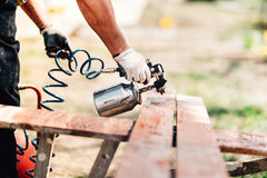 Man painting brown timber, renovating exterior fence during new house design. Industrial man painting brown timber, renovating exterior fence during new house Stock Photography