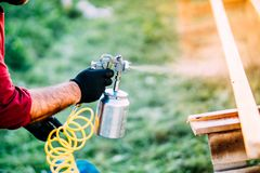 Industrial male worker painting brown timber using spray gun and air compressor royalty free stock image