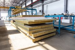 Thermal insulation sandwich panel production line for construction. Manufacturing storage with machine tools, roller conveyor. Industrial manufactory workshop royalty free stock image