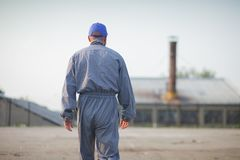 Industrial manufacturing factory worker going to work. Back view of an industrial manufacturing factory worker royalty free stock images