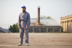 Industrial manufacturing factory worker posing. In front of the factory stock photography