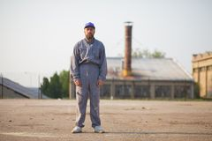 Industrial manufacturing factory worker posing. In front of the factory stock image
