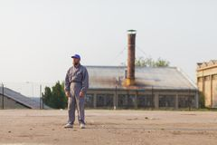 Industrial manufacturing factory worker posing. In front of the factory stock images