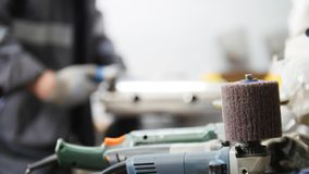 Industrial manufacturing. A man worker on fabric. Sanding machine in focus. Industrial manufacturing. A man worker on fabric. Sanding machine in . Mid shot royalty free stock image