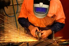 Industrial metal grinding. A tradesman grinding steel on site at a engineering site at a mine. The sparks from the grinder light the gloves and welding shield Royalty Free Stock Photography