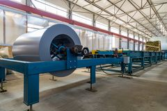 Industrial metal sheet coil in metal sheet profile forming machine in workshop royalty free stock images