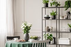 Industrial metal shelf with dishes and plants in bright dining room with round table with chairs. Concept photo royalty free stock photography