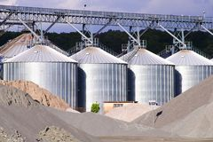 Industrial metal tanks lined up in front of piles of sand royalty free stock image