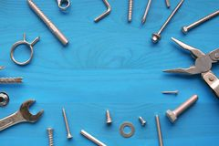 Industrial metal tools - pliers, screws, wrench - on blue wooden background royalty free stock photography