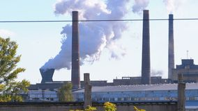 Industrial, metallurgical plant in the city working at full power. Smoke from Pipes. Throws toxic substances into the atmosphere. Heavy smoke, vapor and stock footage
