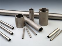 Industrial metallurgy. Steel pipes on gray background. Special-application products (precision pipes Royalty Free Stock Photos