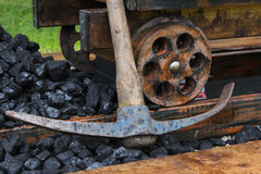 Industrial mine cart scene. Image shows an industrial scene of a coal cart or mine cart on old wooden rails. There is a heap of coal and a pickaxe next to the stock images