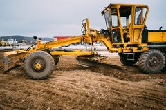 Industrial motor grader working at highway construction site Royalty Free Stock Image