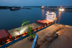 Industrial night. At port - crane is loading ship for transportation Royalty Free Stock Images