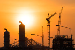 Industrial Oil refinery in building on sunset background at industrial plants Stock Images